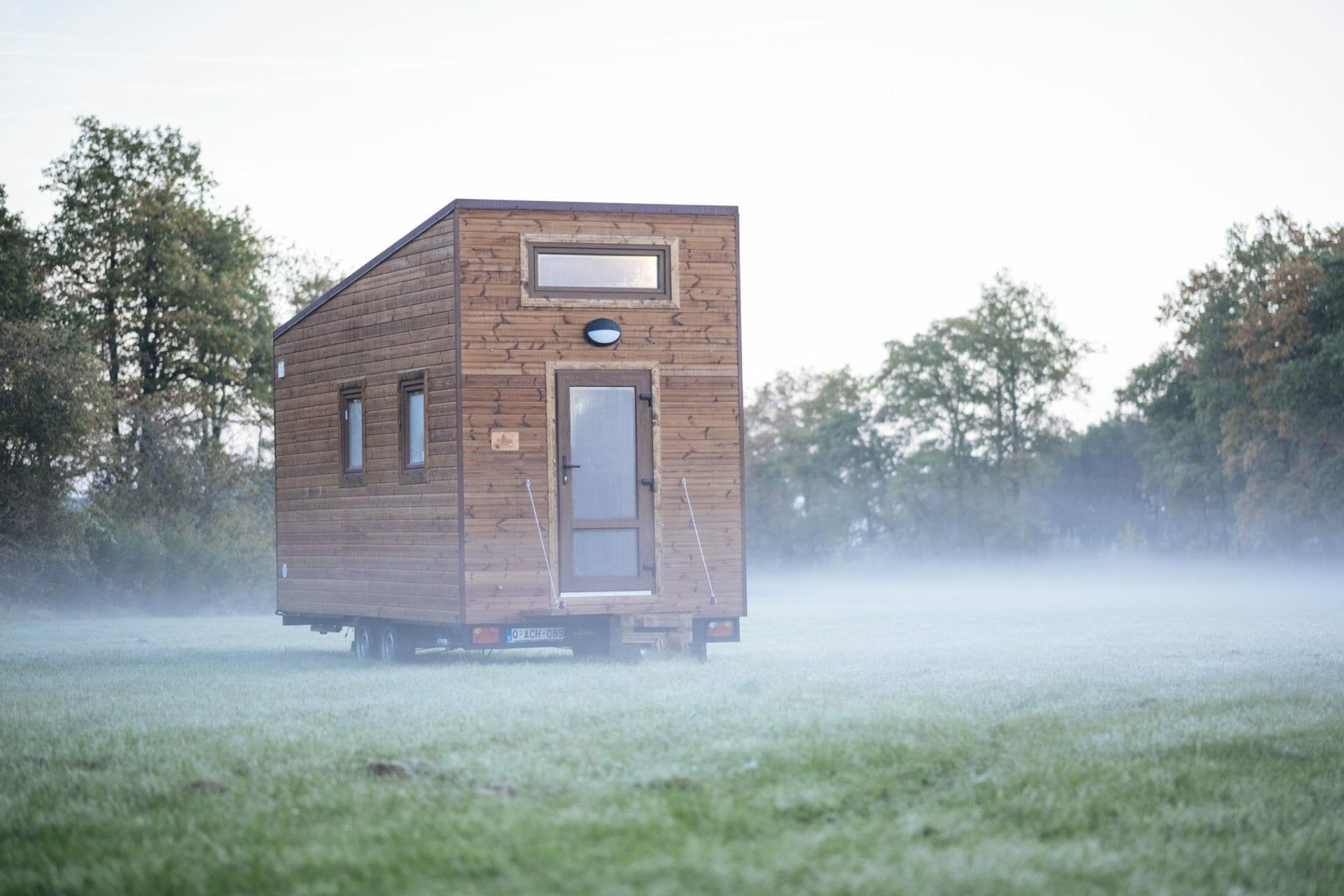 5,50m langes Tiny House auf einer Wiese, umgeben von Nebel