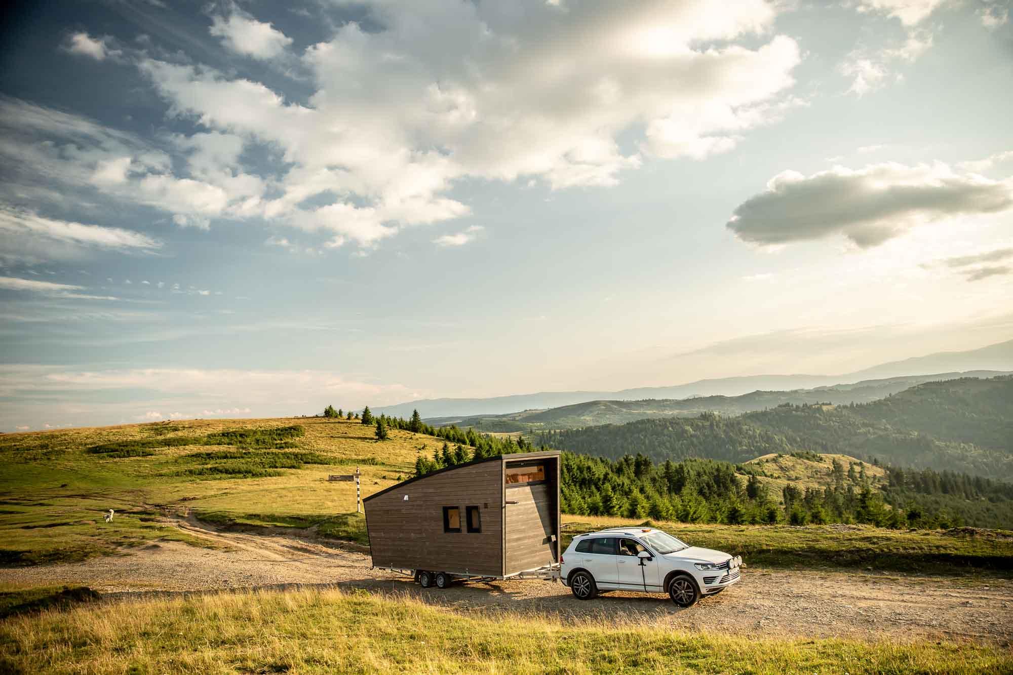 Tiny House auf einem Anhänger, das von einem weißen Geländewagen auf einer Schotterstraße durch die Berge gezogen wird