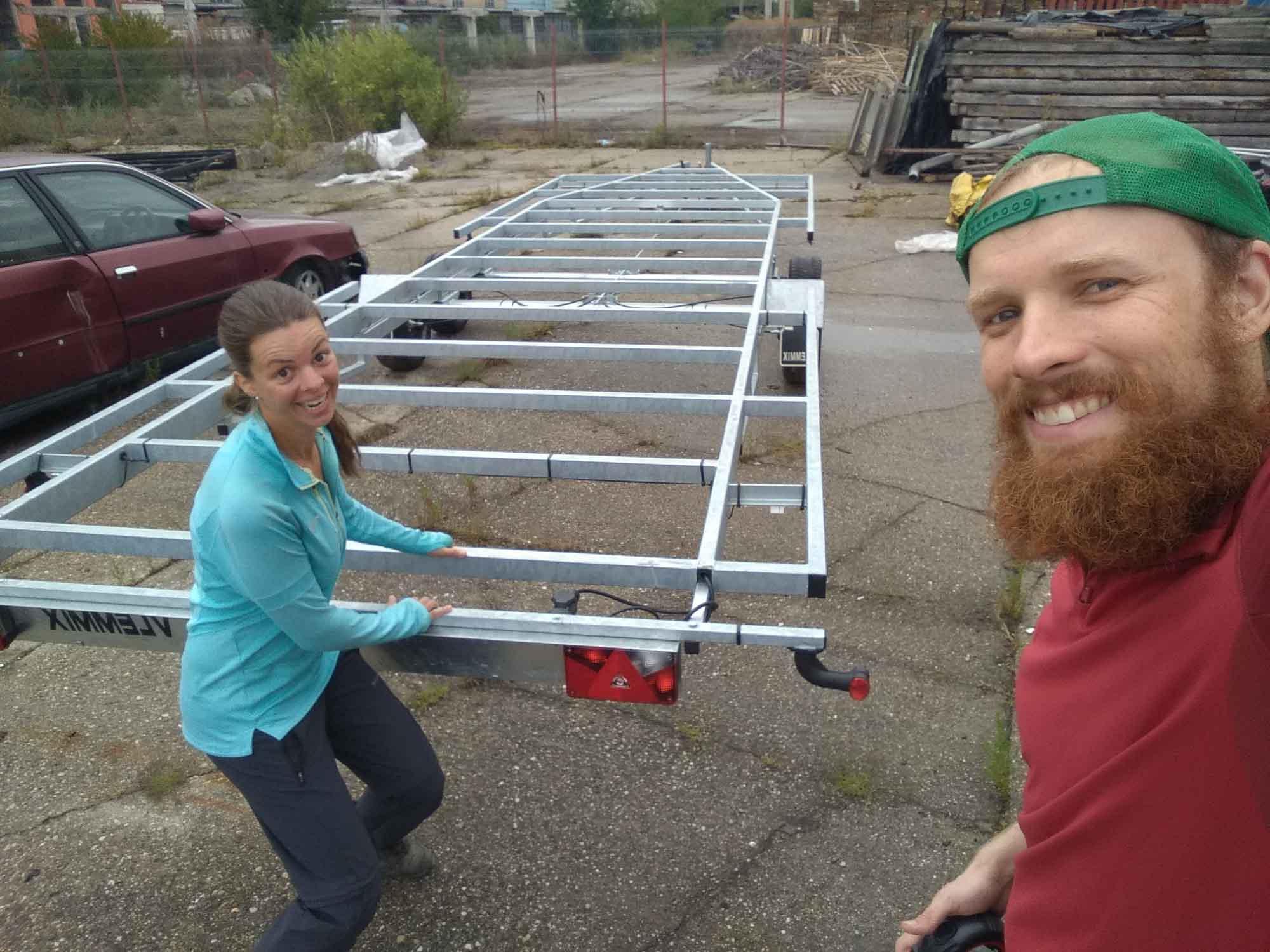 Zwei Personen in guter Stimmung vor einem 7,80m langen Tiny House Anhänger